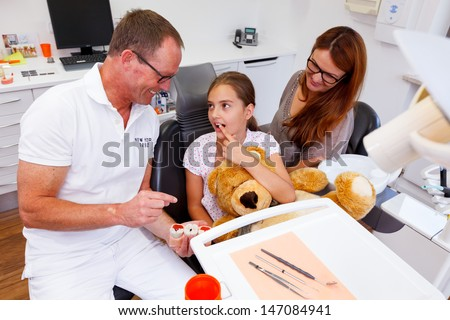 A doctor explains a young family, mother and teenager girl, how they can care the teeth.  - stock photo