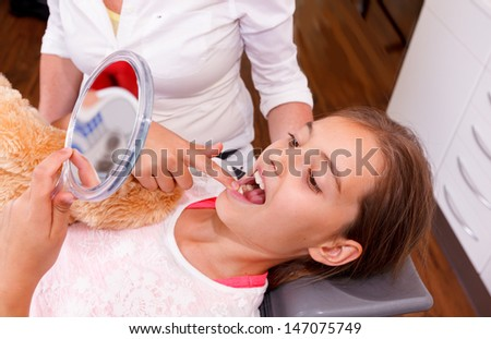 A doctor explains a young girl how she can care the teeth. - stock photo