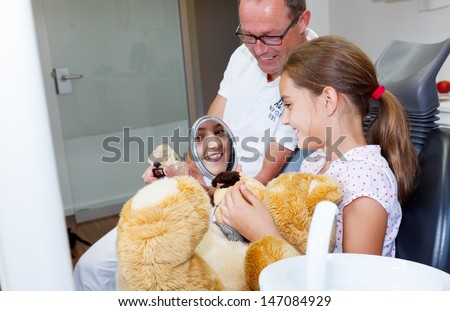 A doctor explains a young teenager girl how she can care the teeth - stock photo