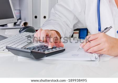 a doctor in the surgery performs administrative work. costs in the doctor's office. - stock photo
