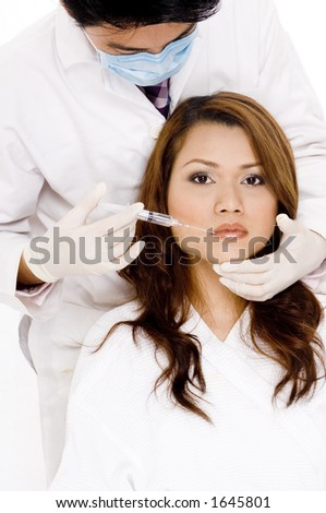 A doctor is about to inject a young woman in the lip