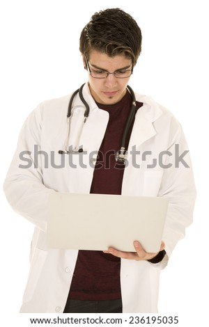 a doctor looking down at his laptop with his stethoscope around his neck. - stock photo