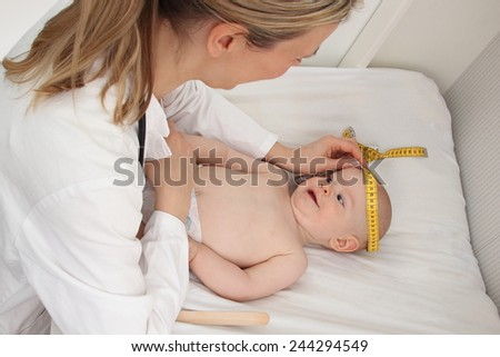 A Doctor measures the head circumference of a Baby - stock photo
