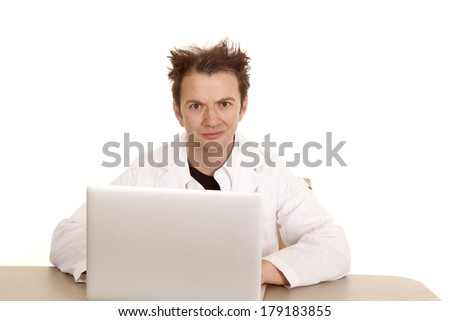 A doctor on a laptop looking with some crazy messed up hair. - stock photo