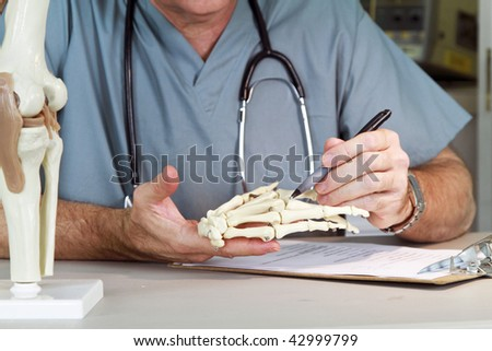 A doctor or intern studying a skeletal model of the human hand.