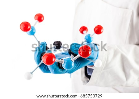 a doctor or researcher with a white lab coat holding a trinitrotoluene tnt molecular model isolated over white