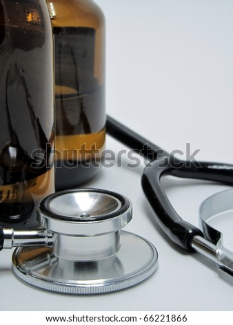 A doctor's stethoscope next to a couple of bottles of medicine
