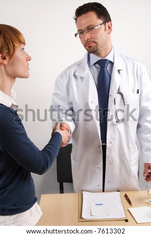 A doctor shakes hands with his patient. - stock photo