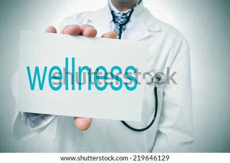 a doctor showing a signboard with the word wellness written in it - stock photo