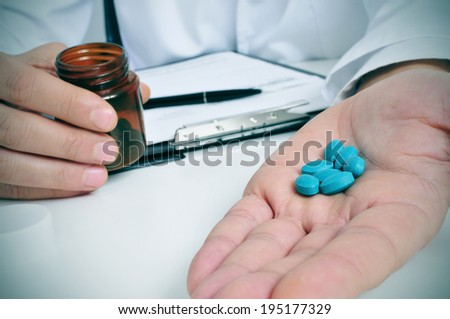 a doctor sitting in a desk with a pile of blue pills in his hand - stock photo
