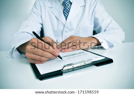 a doctor sitting in the desk of his consulting room writing in a clipboard - stock photo