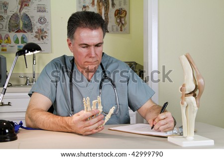 A doctor studying a skeletal model of a human hand, makes some notes.