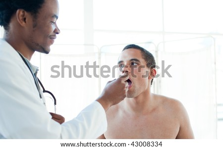 A doctor taking his patient's temperature in a hospital - stock photo