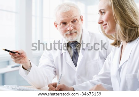 A doctor teaches a student - stock photo