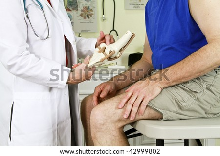 A doctor using a skeletal model of the human knee to explain to her patient the diagnosis of his problem. - stock photo