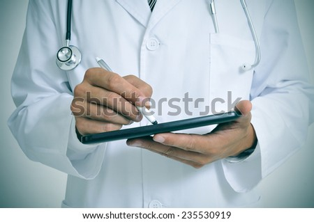a doctor using a stylus pen in a tablet - stock photo