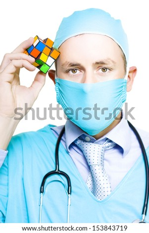 A doctor wearing a mask, stethoscope and surgical gown holds up a colourful puzzle cube to be solved conceptual of seeking a solution to a medical puzzle regarding one of his patients - stock photo