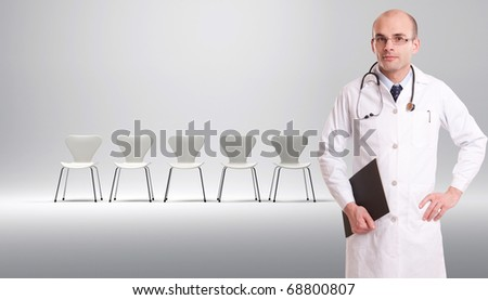 A doctor with a row of white chairs at the background - stock photo