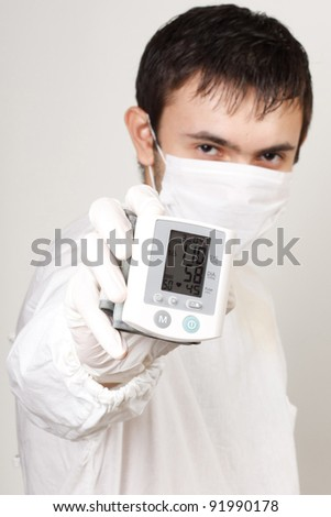 A doctor with an instrument for measuring pressure - stock photo