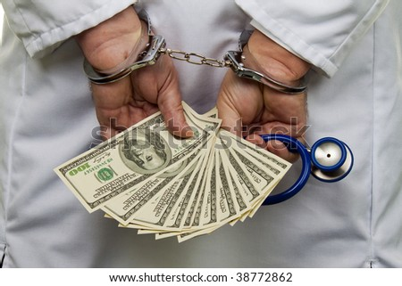 A doctor with dollar bank notes and handcuffs - stock photo