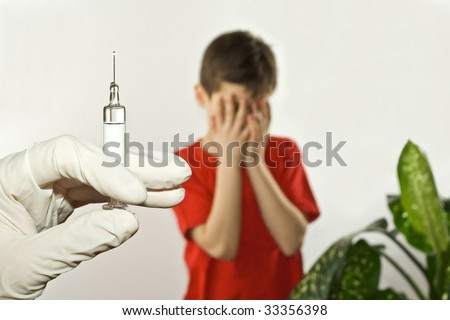 A doctor with gloved hand holding syringe giving a child an injection or an immunization shot - stock photo