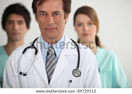 A doctor with his two interns - stock photo