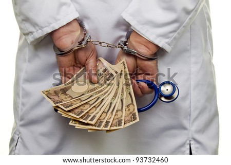 a doctor with japanese yen bank notes and handcuffs - stock photo