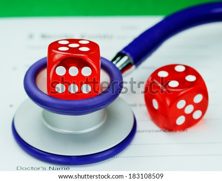 A Doctors dark blue colored stethoscope with a red dice resting on the top of it and one on the pad, both resting on a doctors sick certificate pad, asking the question do you gamble with your health. - stock photo