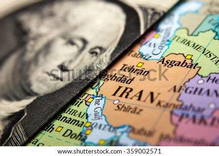 A Dollar bill (figuring George Washington) on top of a map of Iran - stock photo