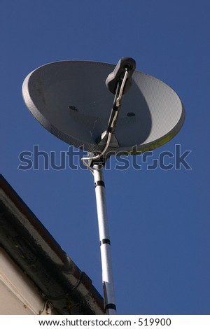 A domestic satellite receiver on a roof. - stock photo