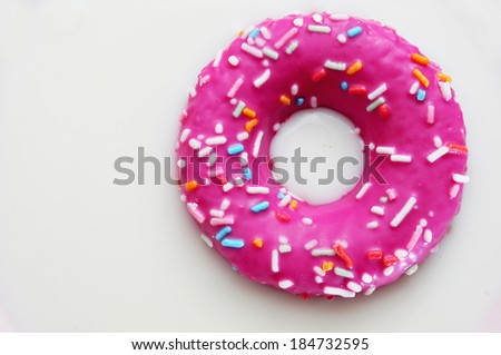 a donut coated with a pink frosting and sprinkles of different colors soaking in milk - stock photo