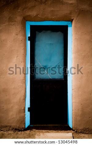 A door in adobe building at Taos Pueblo, New Mexico. - stock photo