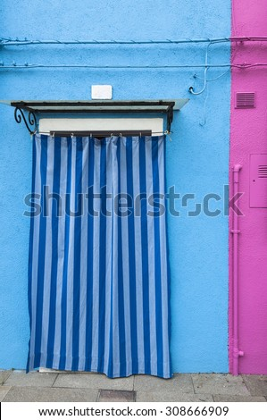 A door on a blue wall from a colorful house of Burano island, Venice, Italy. - stock photo