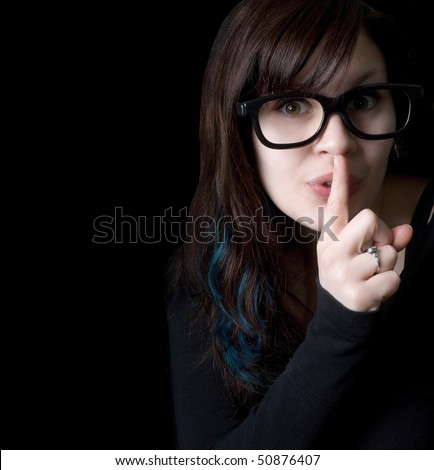 A dorky girl with goofy glasses on black background signaling for quiet with her finger over her mouth. - stock photo