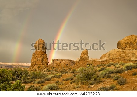 A double rainbow appears after a rainstorm passes over the sandstone formations in Arches National  Park near Moab Utah. - stock photo