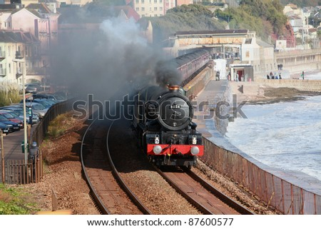 "A ""doubleheader"" locomotive leaves Dawlish station on the famous Brunel line on the south Devon coast taking steam enthusiasts on a nostalgic journey to Plymouth - stock photo"