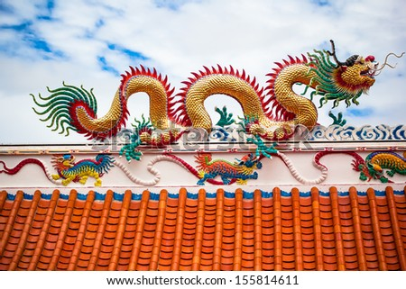 A dragon statue on the Chinese temple roof - stock photo