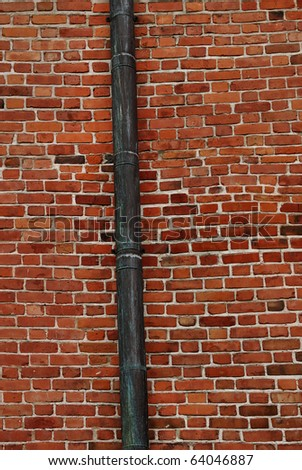 A drain pipe on the side of an old wall building. - stock photo