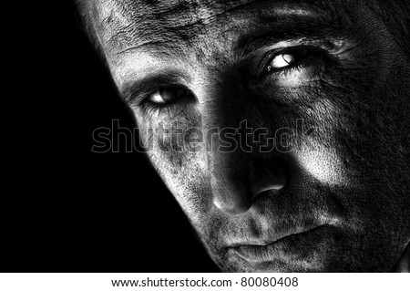 A dramatic black and white image of handsome, confident man staring intently. - stock photo