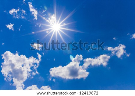 A dramatic blue sky with white clouds and sun - stock photo
