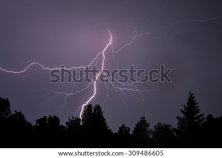 A dramatic bolt of branching lightning silhouettes foreground trees. - stock photo