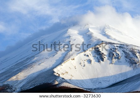 A dramatic close-up of snow covered Mount Fuji - stock photo