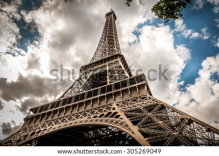 A dramatic perspective of the Eiffel Tower and a moody cloudscape behind it in Paris, France.  - stock photo
