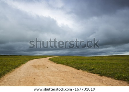 A dramatic scene of the open road with an overcast sky