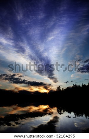 A dramatic sunset over a lake in a forest - Norway