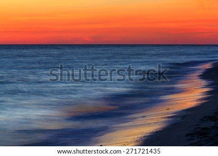 A dramatic sunset sky glows above the sea, photographed with a long exposure for a dreamy, surreal look. Shot on the Gulf of Mexico at Sanibel Island, Florida. - stock photo
