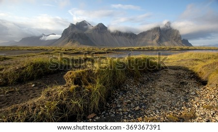 A dramatic view of the mountains overlooking Horni, Iceland with grasslands in the foreground