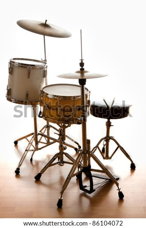 A dramatically back lit drum set ready for a gig - stock photo