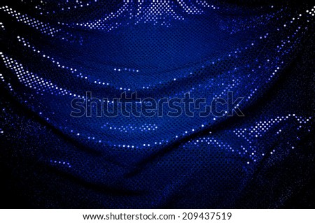 A dramatically draped piece of blue sequined fabric typically used to make dancer's costumes fills the image.  - stock photo
