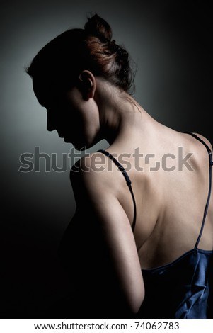 A dramatically lit portrait of a woman in an intimate moment - stock photo